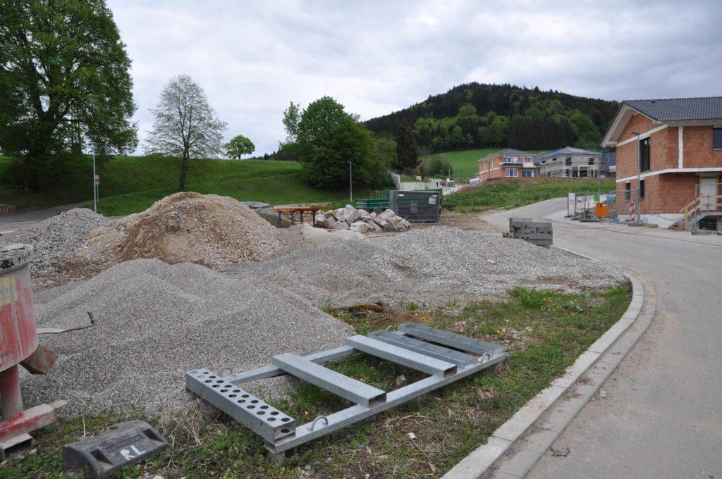"""Das Bauareal """"Alte Ziegelei"""" mit Kies und Baumaterial im Vordergrund und einigen sich im Bau befindlichen Häusern."""