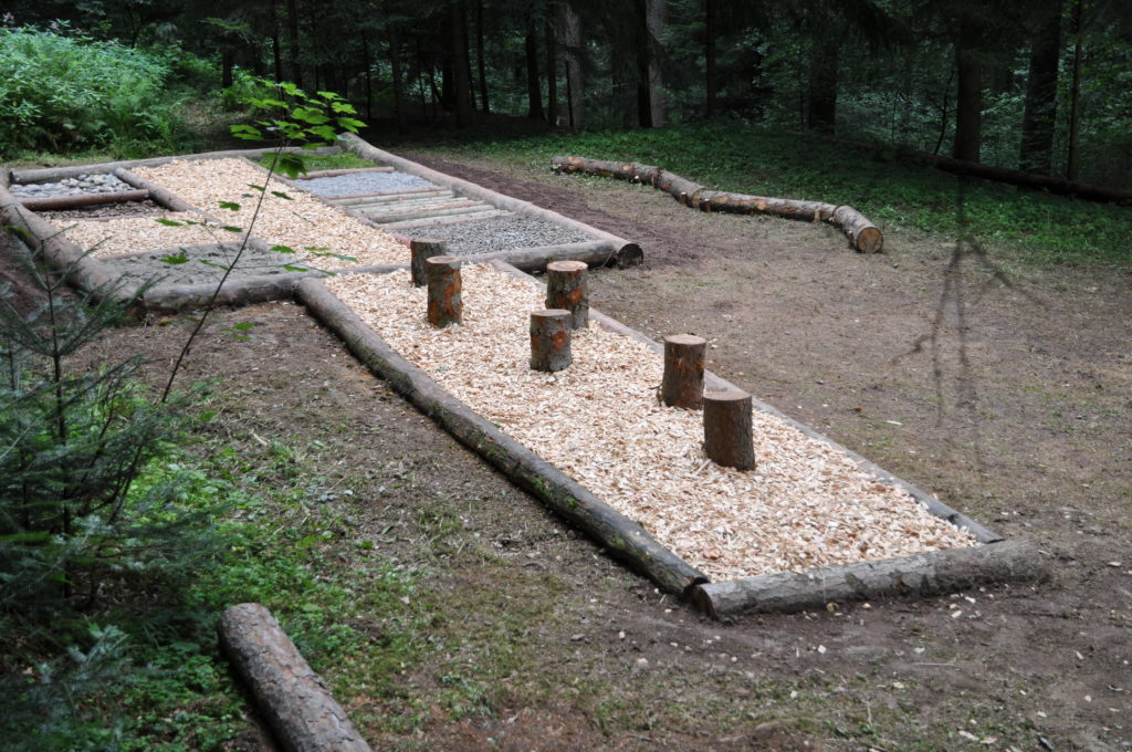 Barfußpfad bestehend aus unterschiedlichen Flächen (Holz, Stein etc.) inmitten eines Waldes gelegen