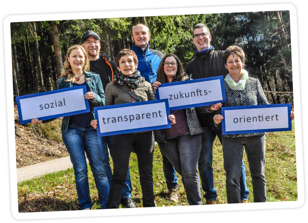 """Gruppenbild der Kandidierenden zur kommenden Gemeinderatswahl 2019, die den Slogan """"sozial, transparent, zukunftsorientiert"""" auf Schildern präsentieren."""