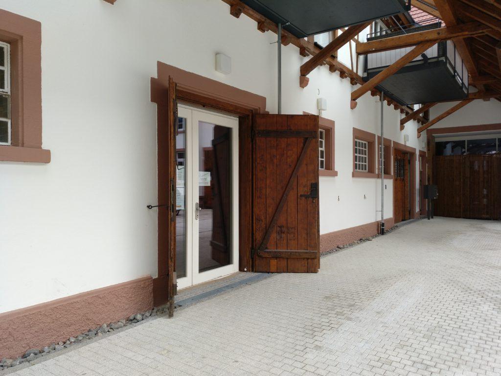 Blick vom Hof aus auf den Eingang des alten Pferdestalls, dessen Holztüren geöffnet sind. Dahinter befinden sich moderne Glastüren. Im oberen Teil des Fotos erkennt man moderne Balkone, die ins Fachwerk des Gebäudes integriert sind.